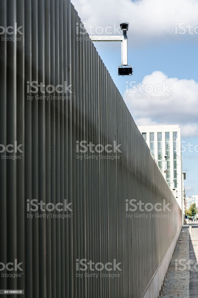 surveillance monitoring security camera on a fence with blue sky stock photo
