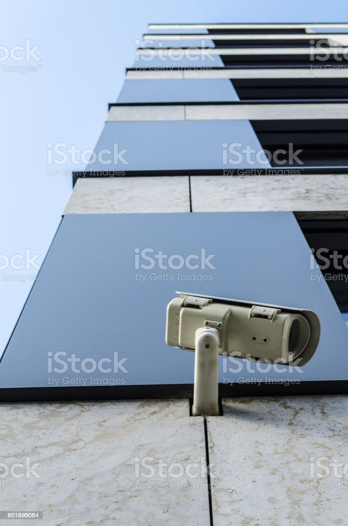 surveillance monitoring security camera on a house corner with blue sky stock photo