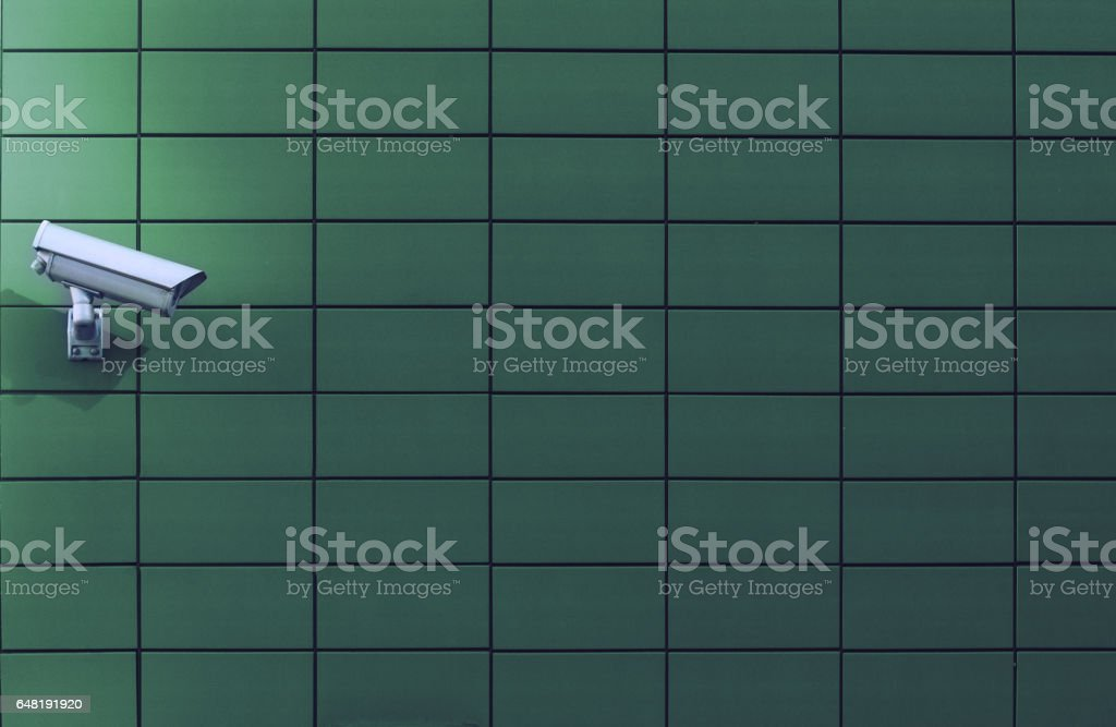 surveillance monitoring white camera on green wall stock photo