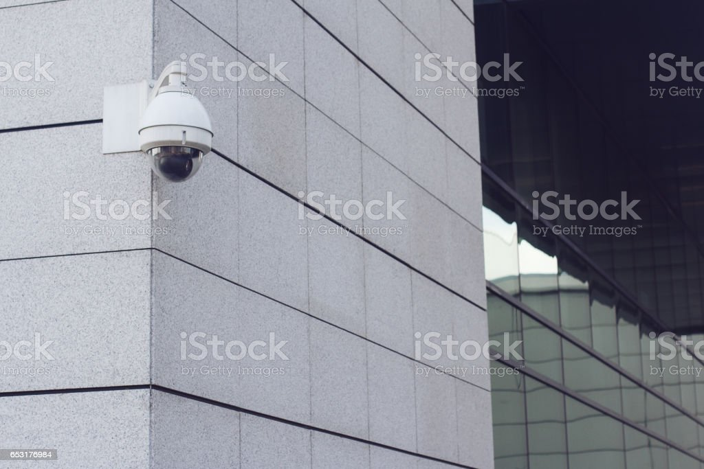 surveillance round camera on building wall stock photo