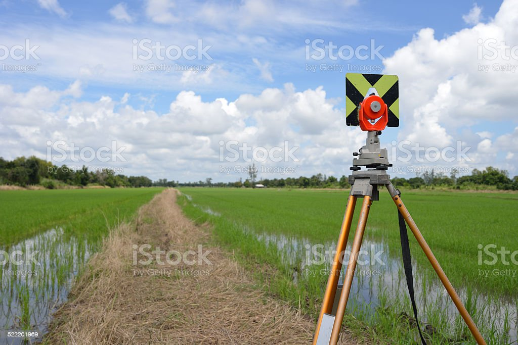 Survey instrument set on a tripod in the field stock photo