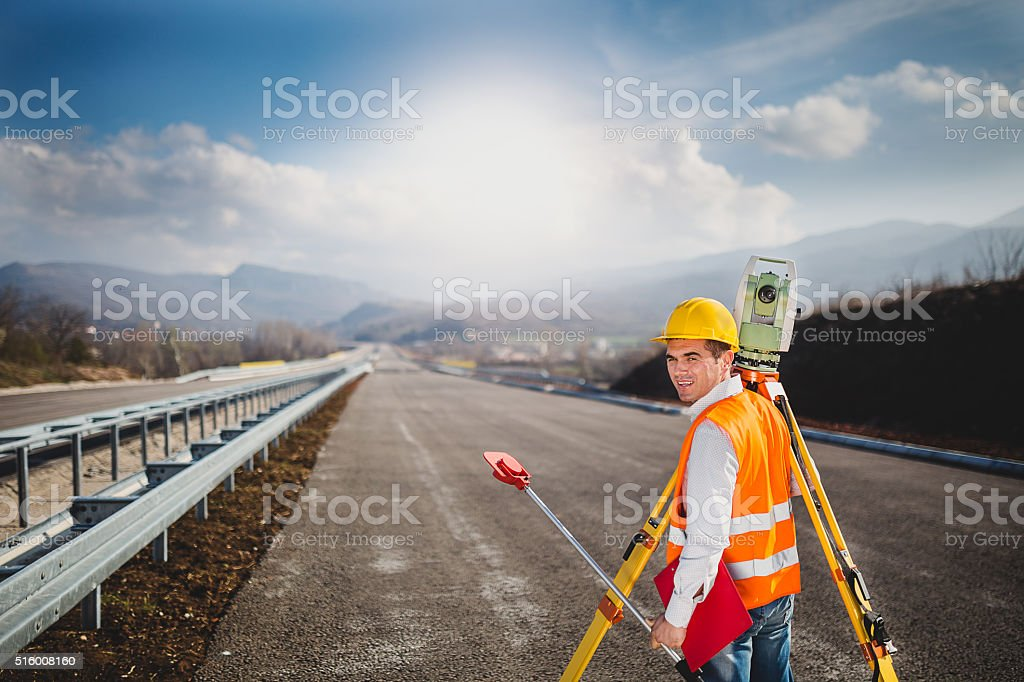 Surveyor changing the digital level position stock photo