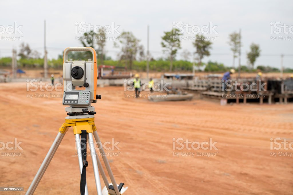 Surveyor equipment tacheometer or theodolite outdoors at construction site and construction worker in safety uniform stock photo