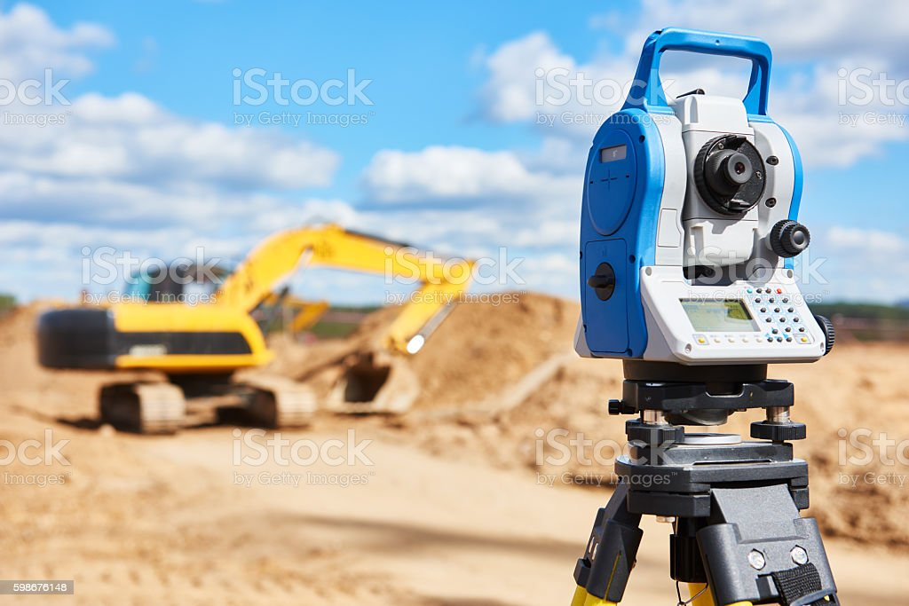 surveyor equipment theodolie at construction site with excavator stock photo