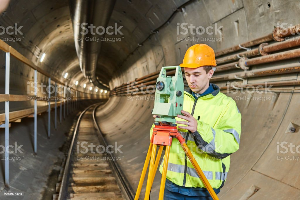 Surveyor with theodolite level at underground railway tunnel construction work stock photo