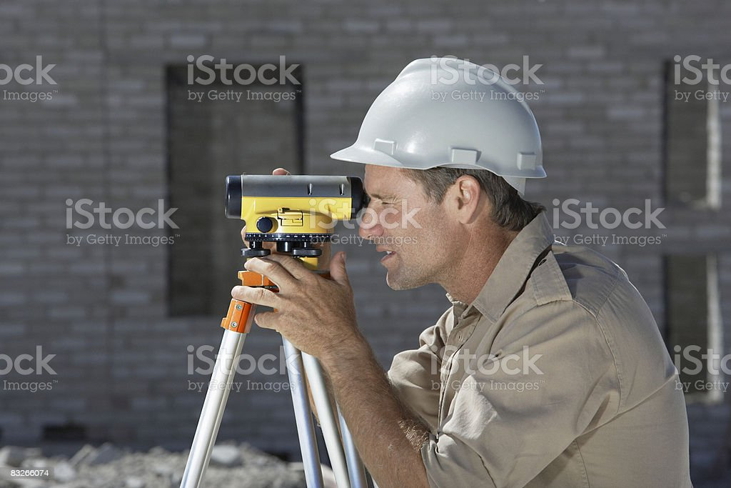 Surveyor working at new construction site royalty-free stock photo