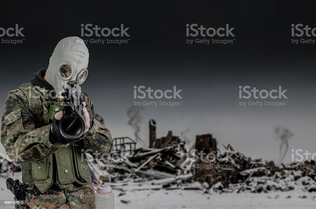 Survivalist pointing a gun at camera with smoking ruins behind stock photo