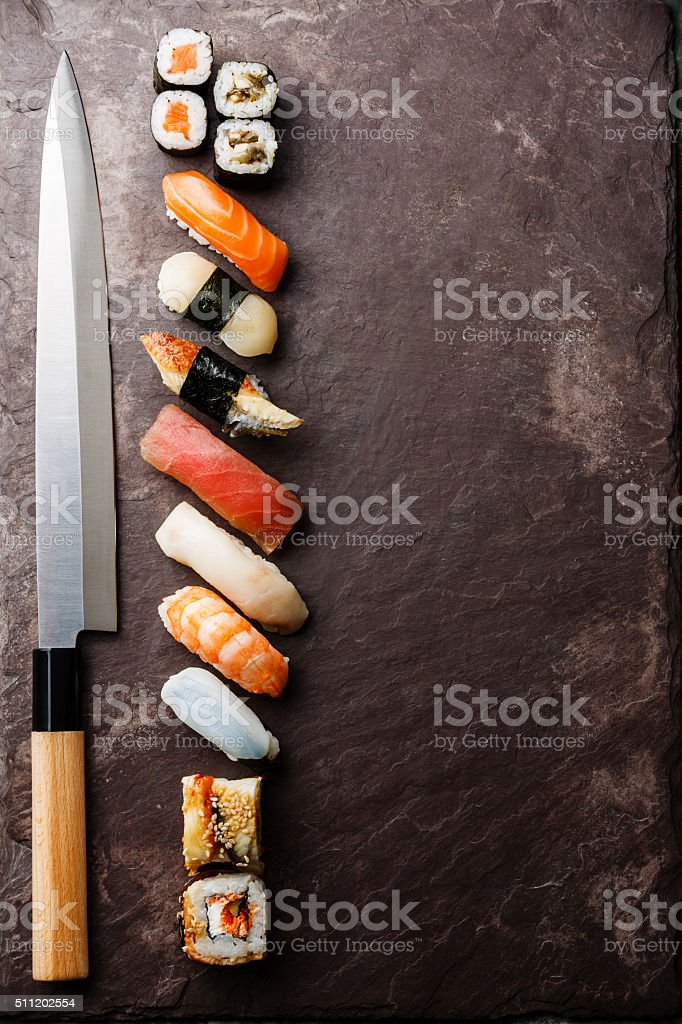 Sushi and knife on stone background stock photo