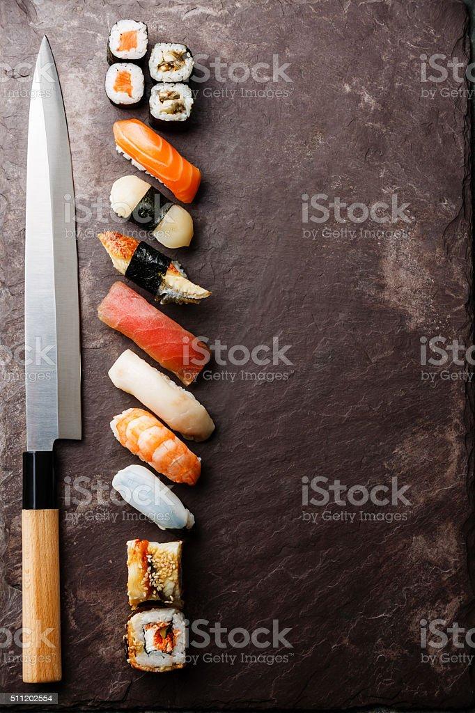 Sushi and knife on stone background stock photo