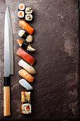 Sushi and knife on stone background
