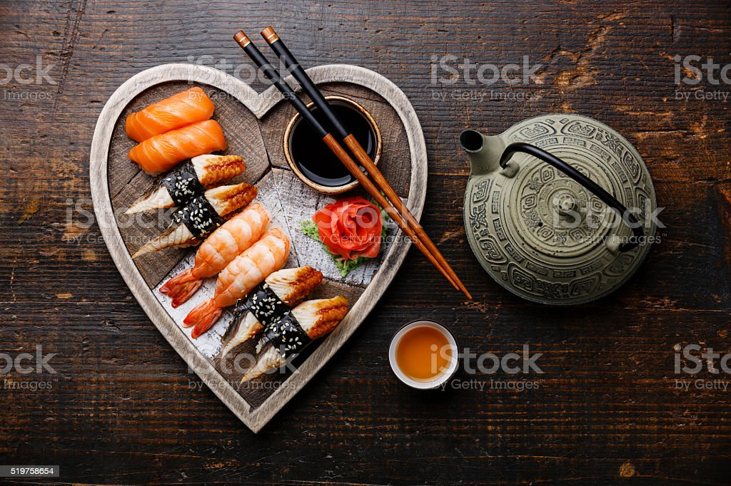 Sushi and tea on Heart shape wooden tray stock photo