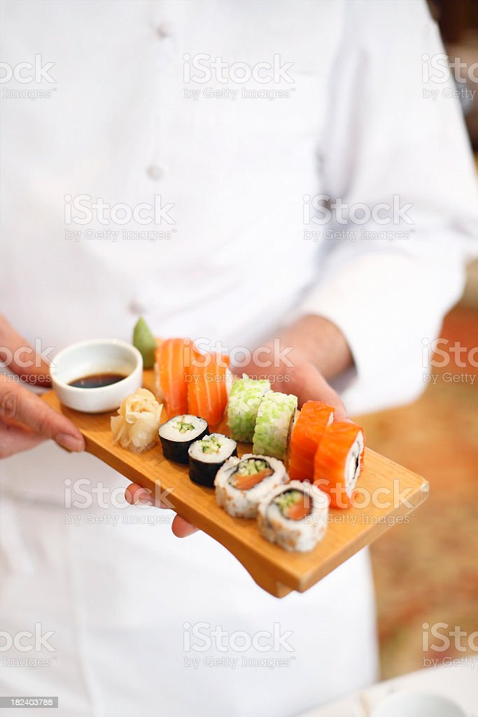 Sushi chef holding a tray of fresh sushi on a wood plater royalty-free stock photo