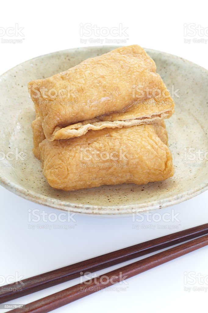 Sushi flavored boiled rice wrapped in fried tofu stock photo