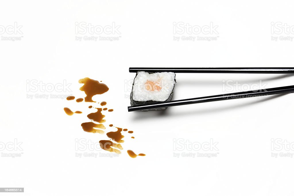 Sushi Hosomaki in The Chopsticks. Typical Japanese Food royalty-free stock photo