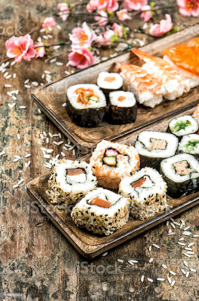 Sushi, maki, sashimi and sushi rolls. Spring flowers stock photo