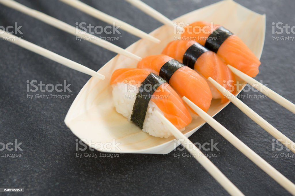 Sushi on boat shaped plate with chopsticks royalty-free stock photo