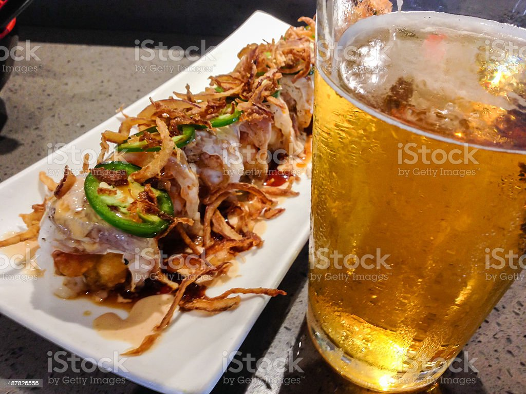 Sushi roll and glass of beer on sushi bar stock photo