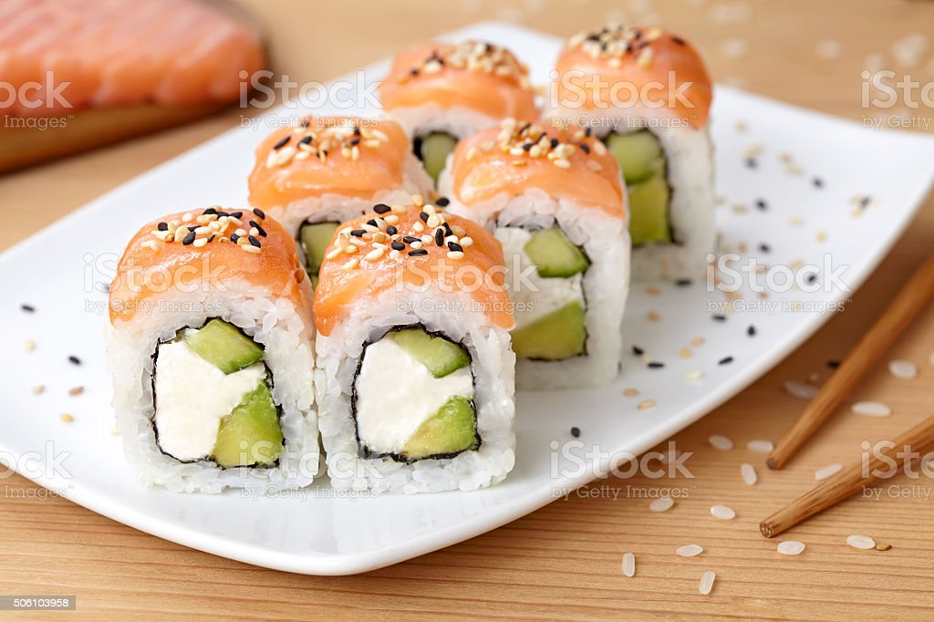 Sushi roll with feta cheese, avocado, cucumber, salmon and sesame stock photo