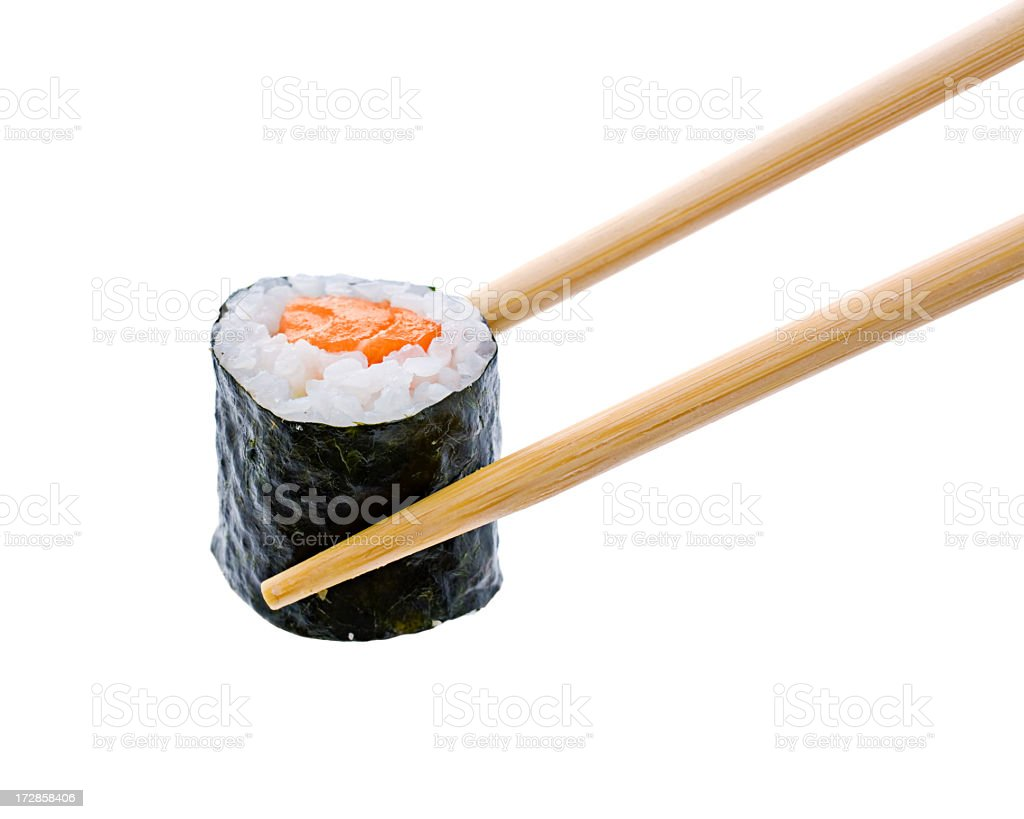 A sushi roll with salmon being held by wooden chopsticks royalty-free stock photo