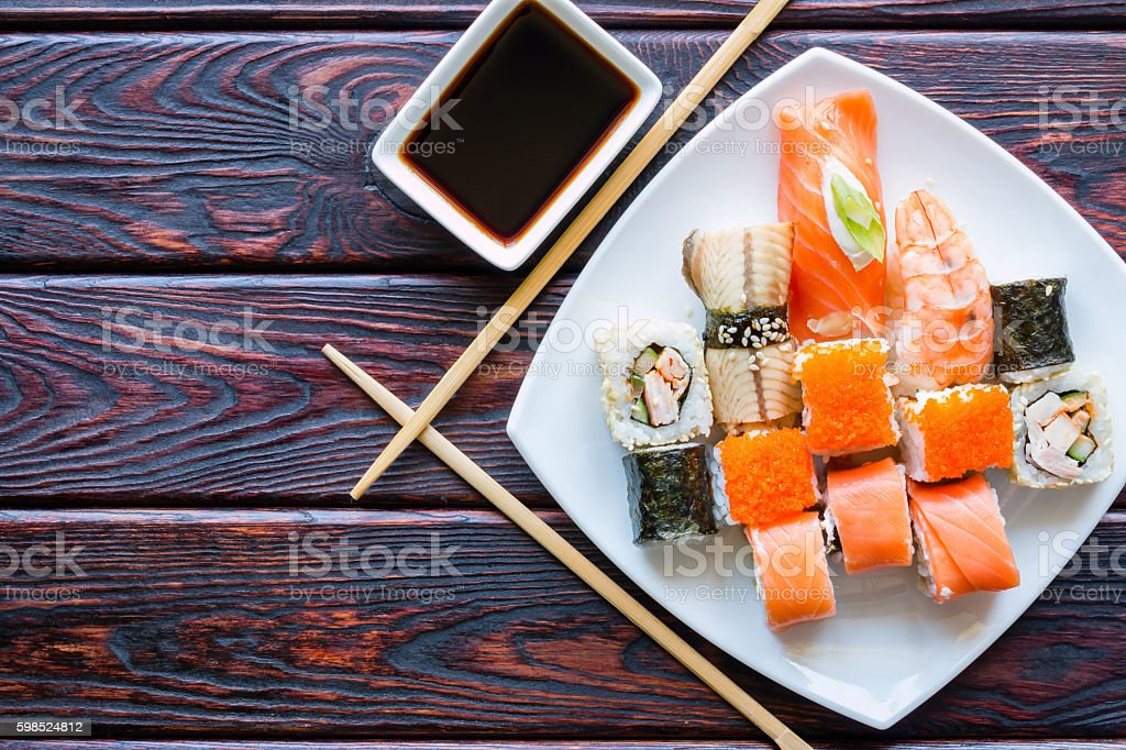 sushi rolls on a white plate and chopsticks stock photo