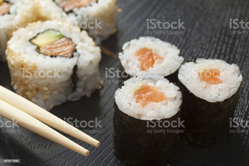 sushi rolls  on black plate and chopsticks stock photo