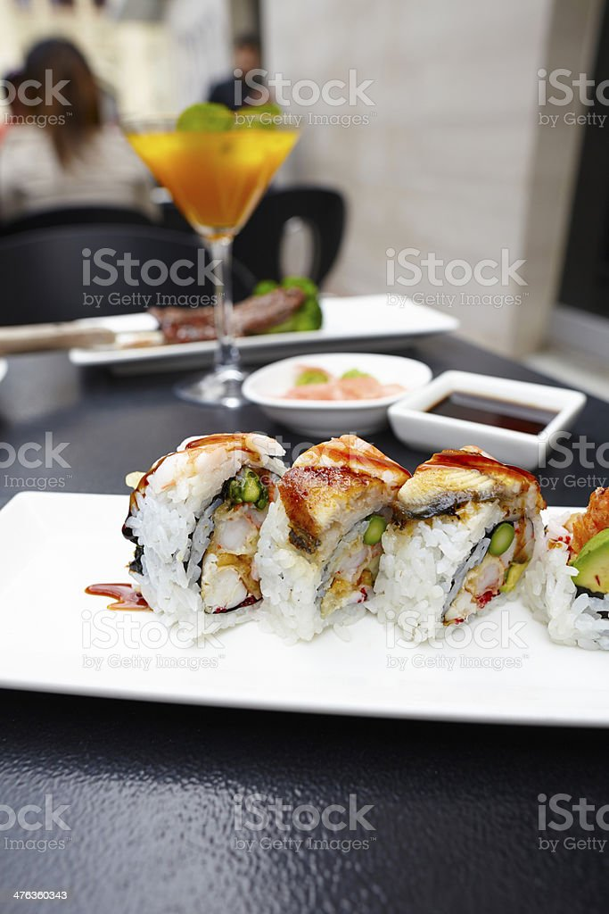 Sushi rolls on plate with cocktail drink outdoors royalty-free stock photo