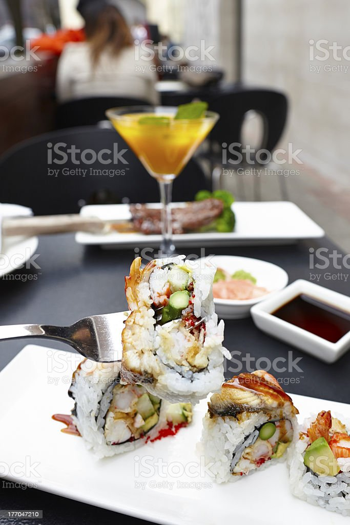 Sushi rolls on plate with fork holding outdoors royalty-free stock photo