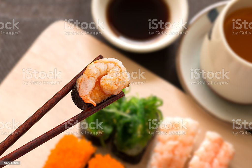 Sushi set with chop sticks, wasabi served on wooden slate, stock photo
