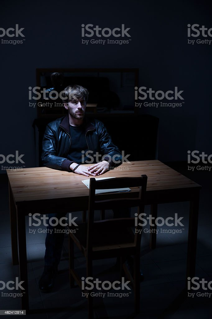 Suspect man in interrogation room stock photo