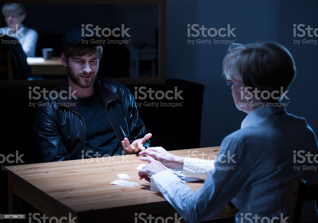 Suspect responding to policewoman questions stock photo