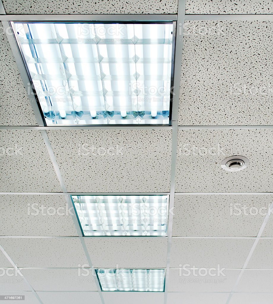 Suspended ceiling with fluorescent lighting and smoke detectors stock photo