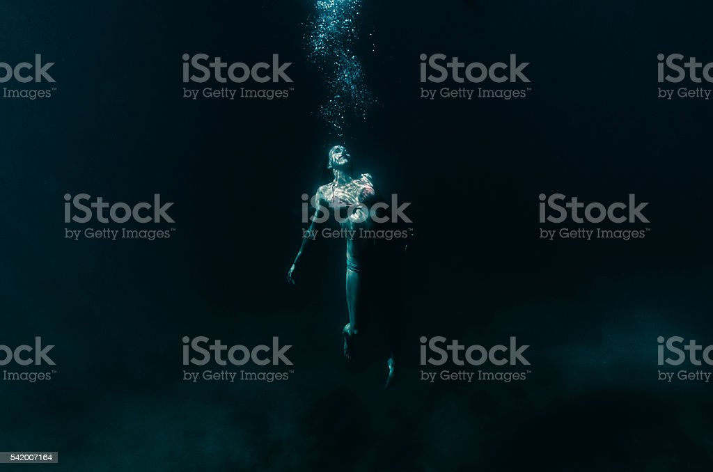 suspended in dark water all alone stock photo