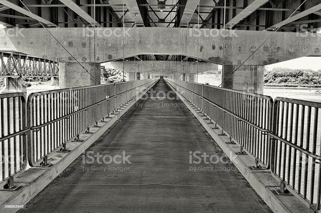 Suspended Pedestrian Walkway Beneath Traffic Bridge in Saskatoon stock photo