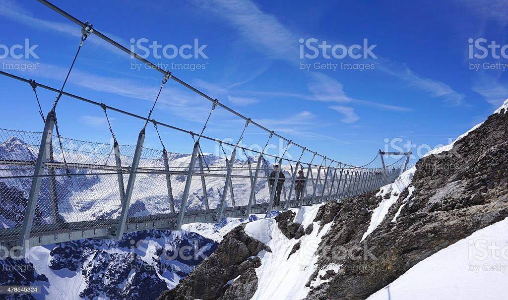 Suspended walkway over snow mountains stock photo