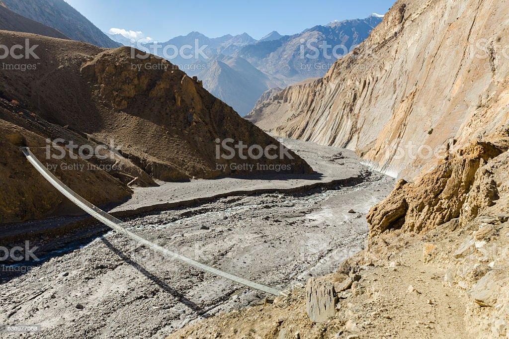 suspension bridge across mountain river, Himalayas, Nepal stock photo