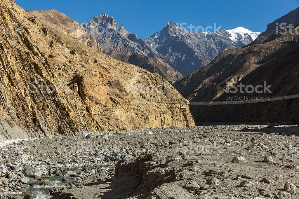 suspension bridge across mountain river, Himalayas Nepal stock photo