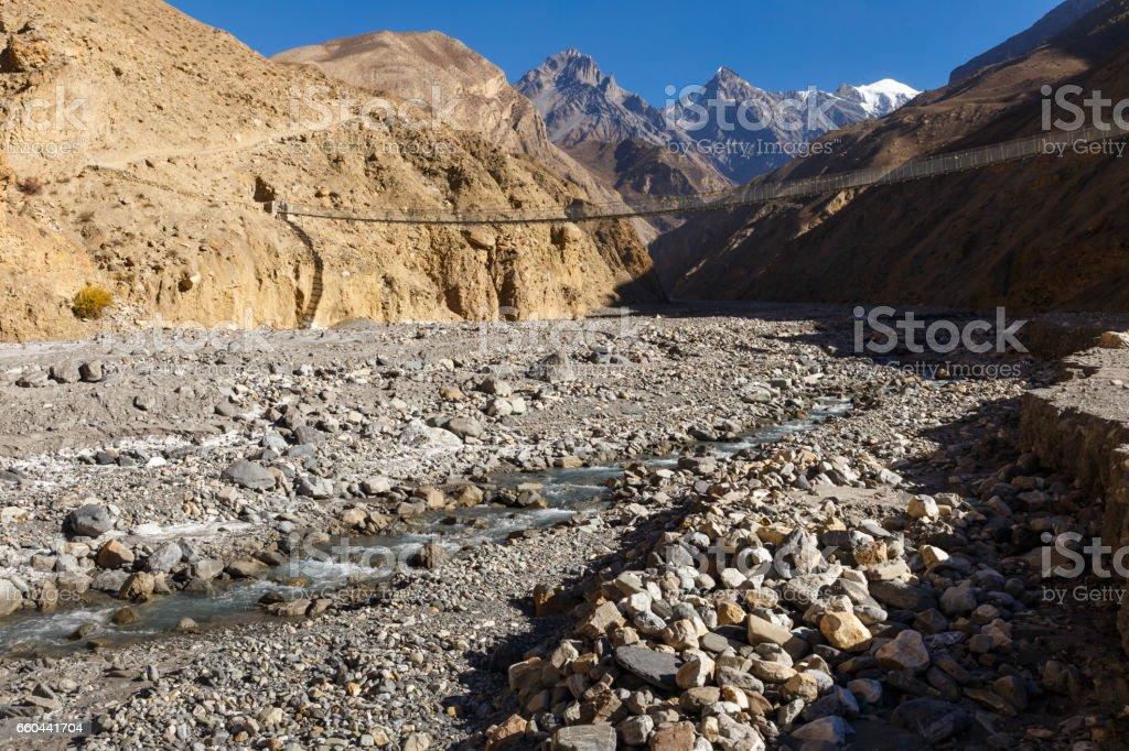 suspension bridge across mountain river, Himalayas stock photo