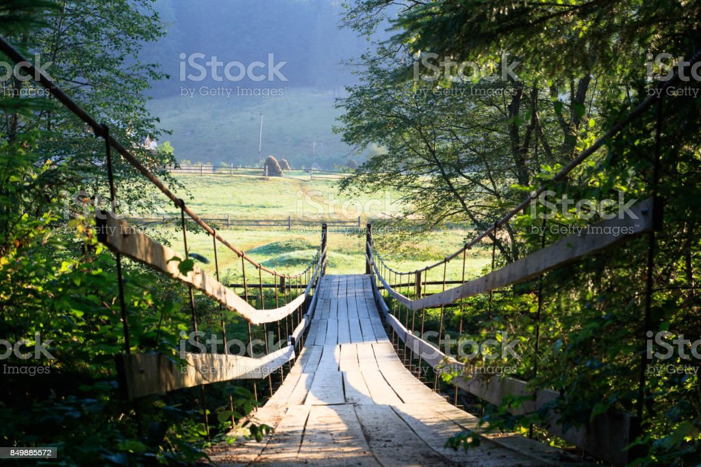 suspension bridge across the river. morning time. Stack of hay on the glade on the other side of bridge. green trees stock photo