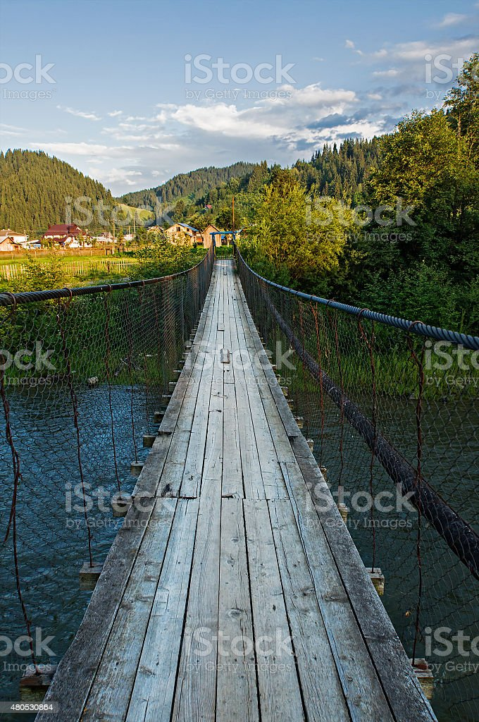 Suspension bridge over the river in the mountains stock photo