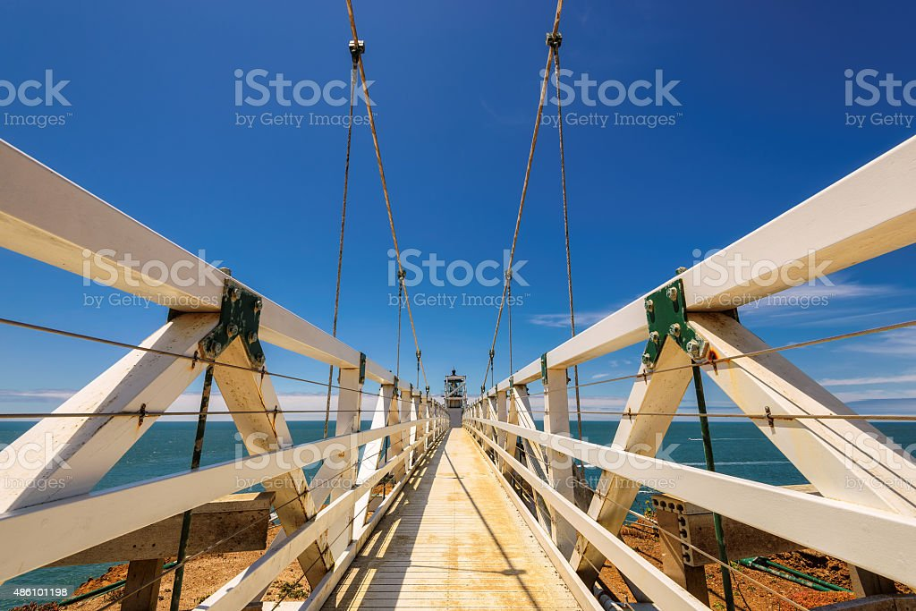 Suspension bridge to Lighthouse under blue sky stock photo