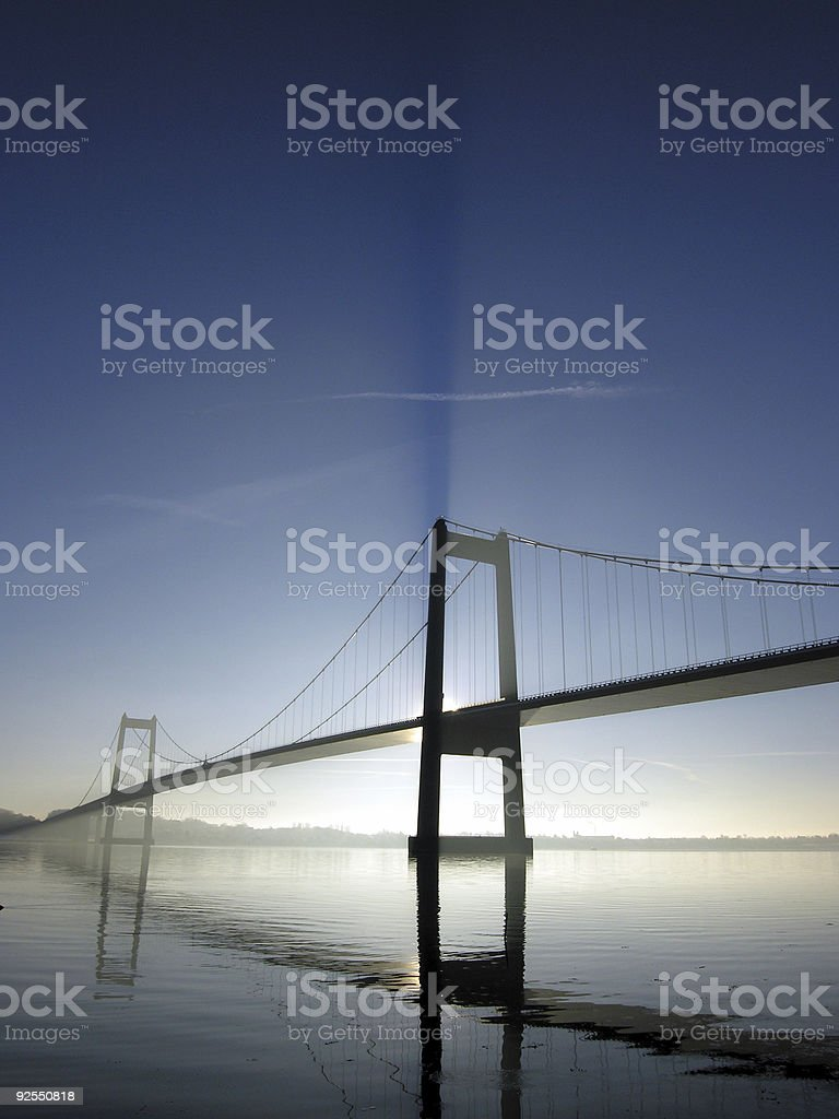 Suspension bridge with reflection in still water stock photo