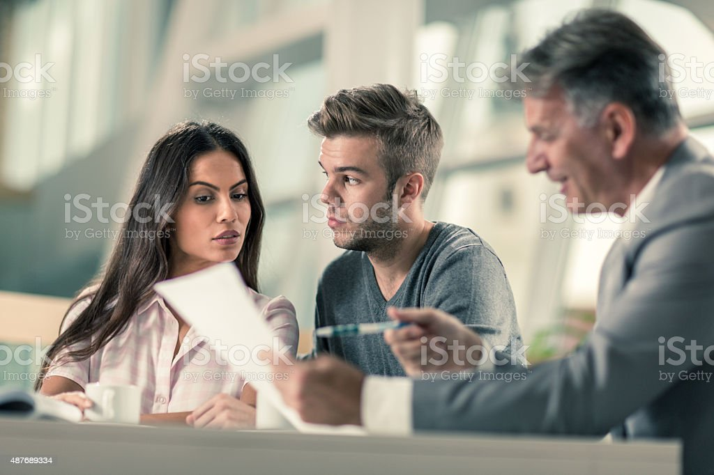 Suspicious couple having a business meeting with real estate agent. stock photo