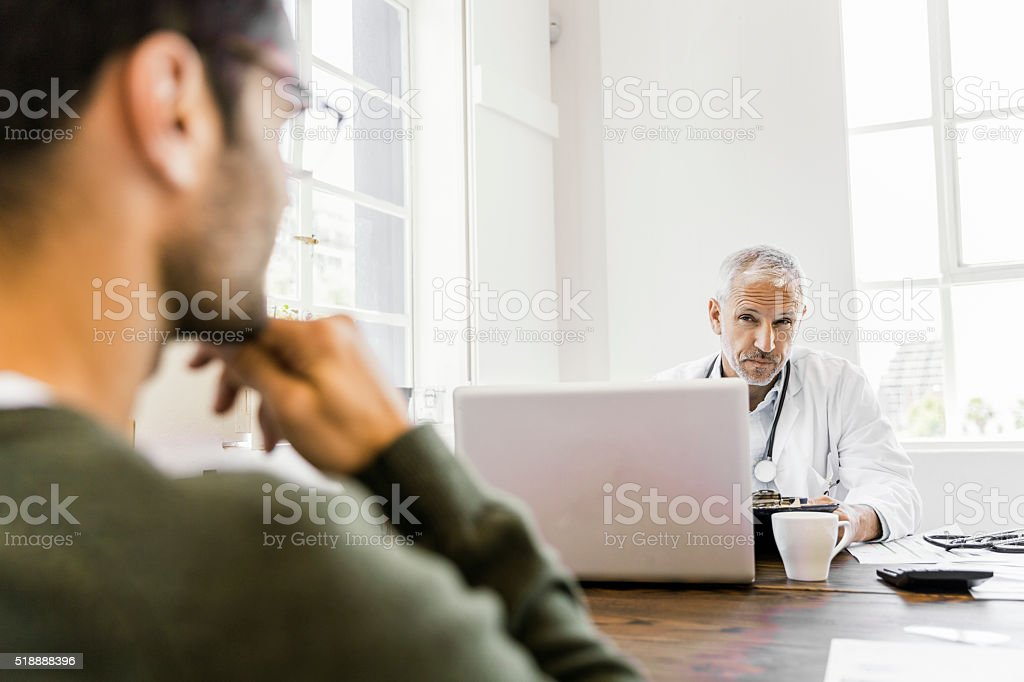 Suspicious doctor looking at patient in clinic stock photo