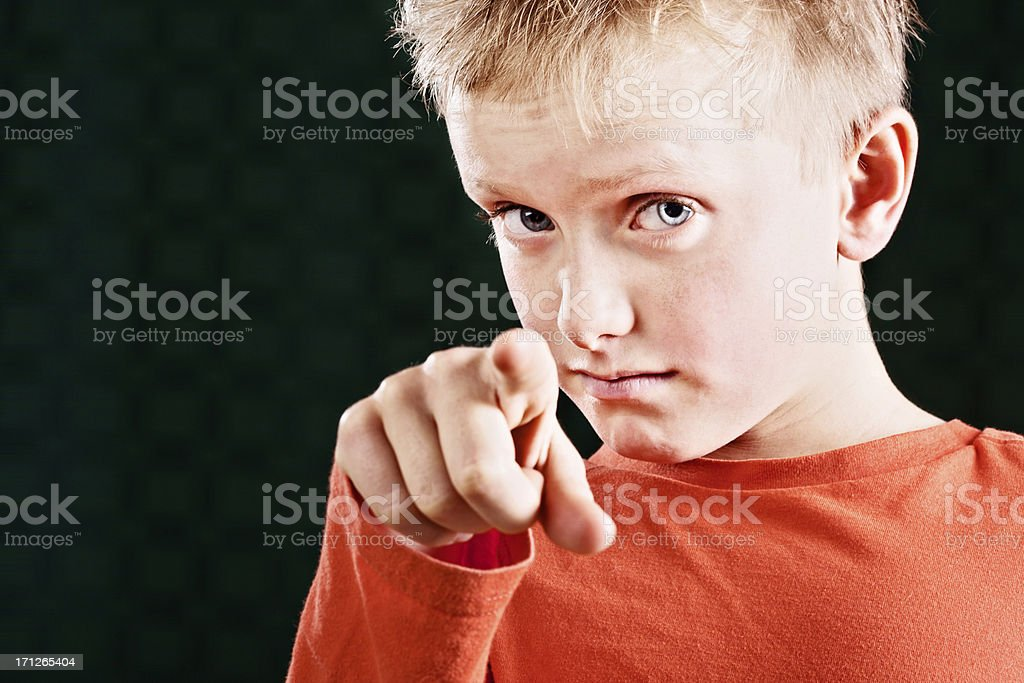 Suspicious little boy points a finger accusingly stock photo