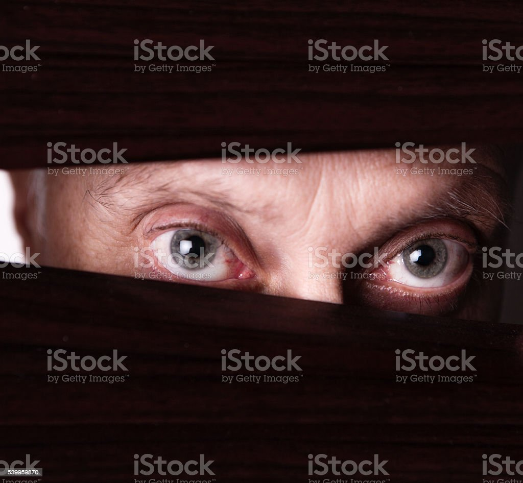 Suspicious man looking out or spying through blinds stock photo