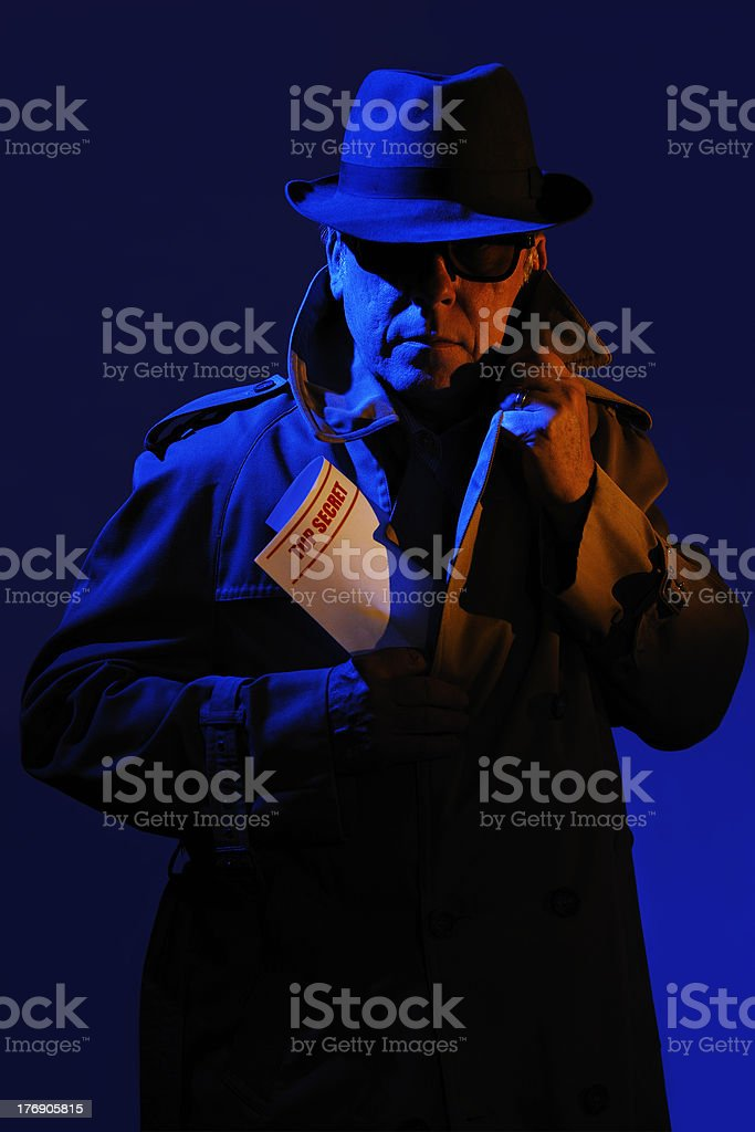 Suspicious man wearing a trench coat holding top secret papers. stock photo