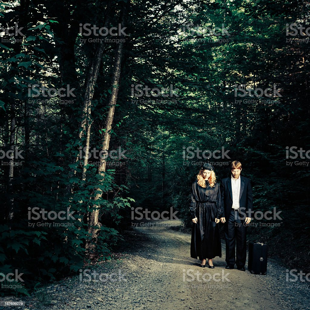 suspicious young couple elegantly dressed on a dirty road royalty-free stock photo