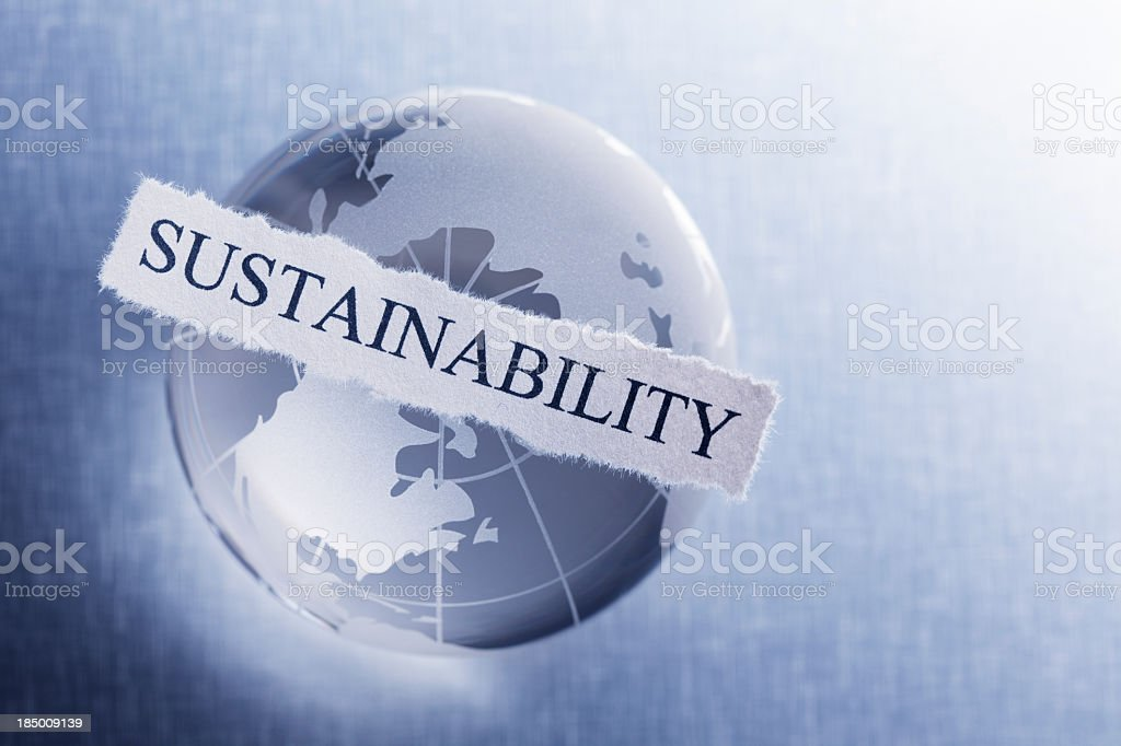 Sustainability printed on torn paper on top of globe royalty-free stock photo
