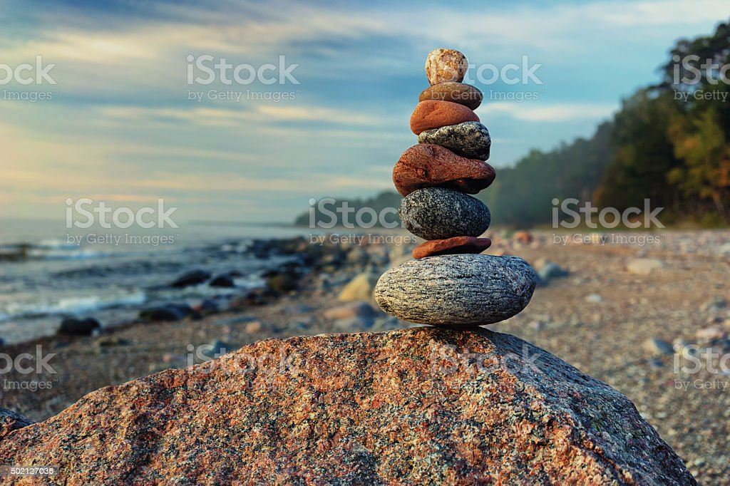Sustainable cairn at sea in pastel colors stock photo