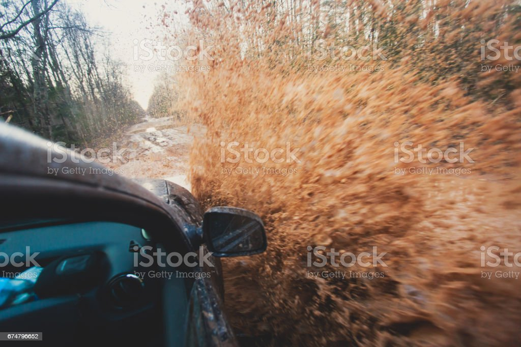 Suv 4wd car rides through muddy puddle, off-road track road, with a big splash, during a jeeping competition stock photo